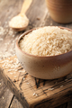 Uncooked parboiled rice in a bowl on wooden table - PhotoDune Item for Sale