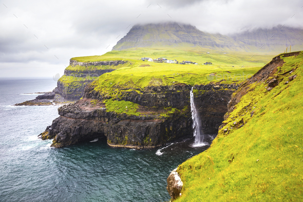 Dramatic waterfall on Faroe Islands and the village Gasadalur - Stock Photo - Images