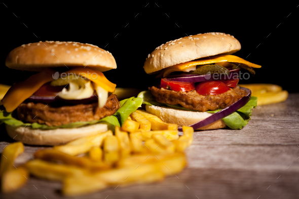 Classic cheeseburgers on wooden plate - Stock Photo - Images