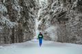 Girl Athlete Running in Winter Forest