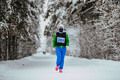 Girl Athlete Running Snow-Covered Alley