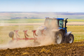 tractor ploughing a field with trail of dust