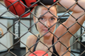 Portrait of female boxer looking through metal fencing