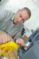 Senior technician using multi meter to test electrical appliance