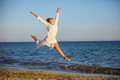 Young woman jumping with joy on beach
