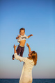 Happy young woman throwing little son up in air on beach