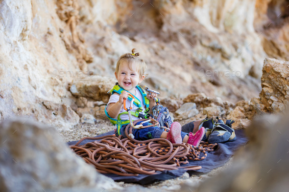 Happy little girl playing with rock climbing equipment