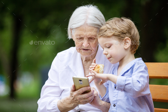 Young boy and his great grandmother using smartphone outdoors