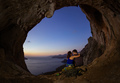 Romantic couple of rock climbers in cave at sunset