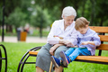 Young boy and his great grandmother using tablet in park