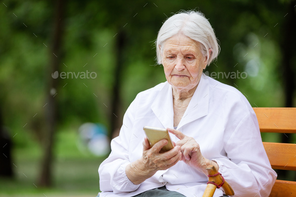 Senior woman using smartphone while sitting on bench in park