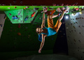 Young woman bouldering along ceiling in indoor climbing gym