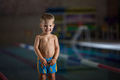 Happy little boy standing on side of swimming pool
