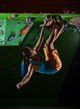 Young woman bouldering on ceiling in climbing gym