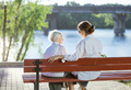Senior woman and her adult granddaughter sitting on bench in park