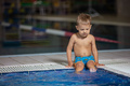 Little boy sitting poolside and dangling legs in water