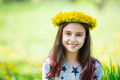 Cute young girl wearing wreath of dandelions and smiling
