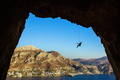 Silhouette of a rock climber hanging on rope while climbing in cave,
