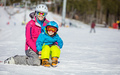 Cheerful mother and son resting on ski slope
