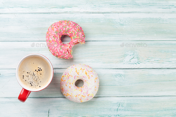 Coffee cup and colorful donuts - Stock Photo - Images