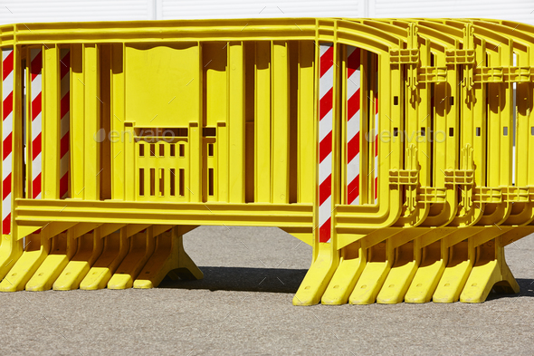 Yellow plastic barrier fence over an asphalt road. Security - Stock Photo - Images