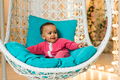 Portrait of mixed race child at home sitting in the armchair