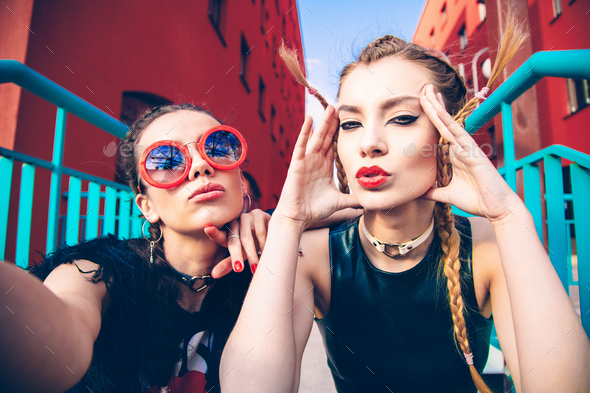 two young positive women having fun and making selfie