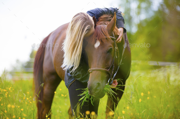 Blonde woman standing in a meadow hugging her arabian horse - Stock Photo - Images