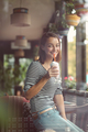 A woman sits on the summer terrace of a city cafe and drinks a milkshake