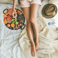 Young girl taking fig from tray full of fresh fruits