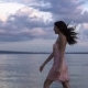 Girl in Cocktail Dress Carefree Walks on the Beach at Sunset