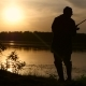 Fisherman Catches Fish on a Fishing Rod Sunset Beautifully Wraps His Silhouette