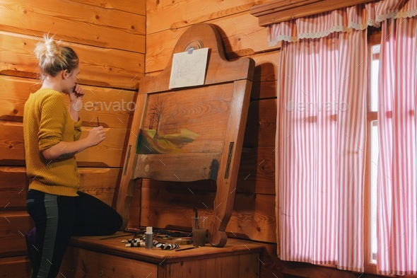 female artist painting a landscape picture on a reclaimed wooden board-art is property released - Stock Photo - Images