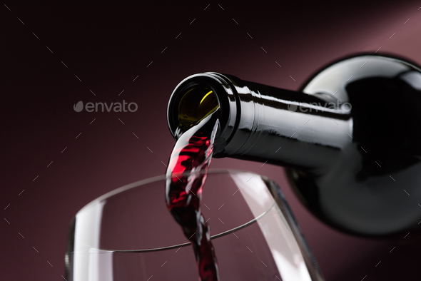 Pouring red wine into a wineglass - Stock Photo - Images