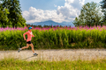 Woman trail running on country road in mountains, summer day