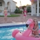 Little Girl In Swimsuit Jumping Into Summer Poolside, Pretty Child in Inflatable Flamingo Swim in