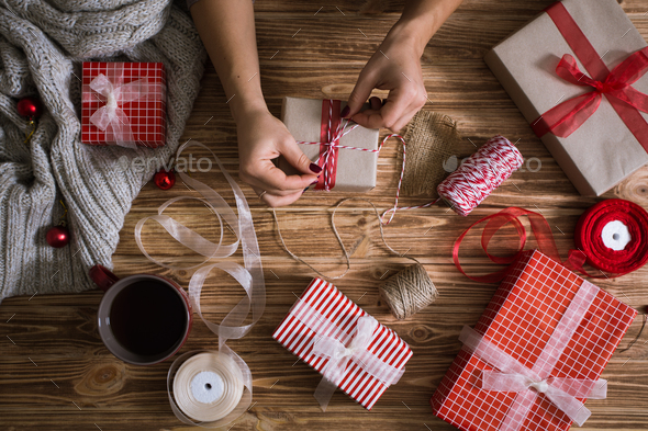 Female hands wrapping Christmas presents in paper and tying them with red and white threads - Stock Photo - Images