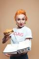 Mature redhead fashion woman eating burger. Looking camera.