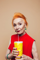 Serious mature redhead fashion woman drinking aerated water