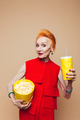 Smiling mature redhead fashion woman eating popcorn