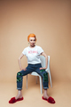 Mature redhead fashion woman sitting isolated