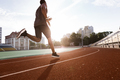 Athlete african man running on racetrack