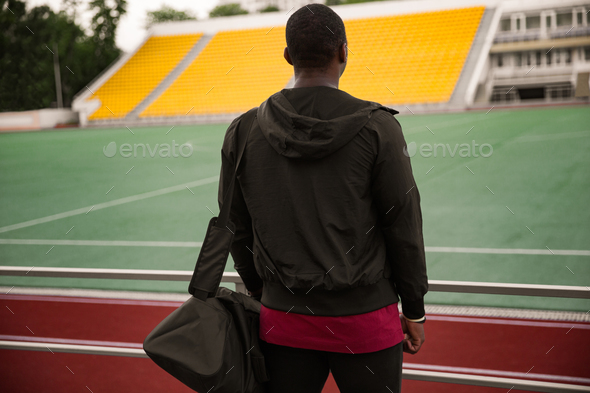 Back view of a athletic man with bag standing at the stadium