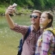 A Young Couple of Tourists Doing Selfie on the Background of a Mountain River. Take Pictures By - VideoHive Item for Sale