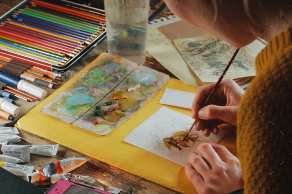 female artist painter paiting a watercolor picture of a bear-art is property released - Stock Photo - Images