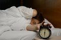 woman turning off the alarm clock on the bed