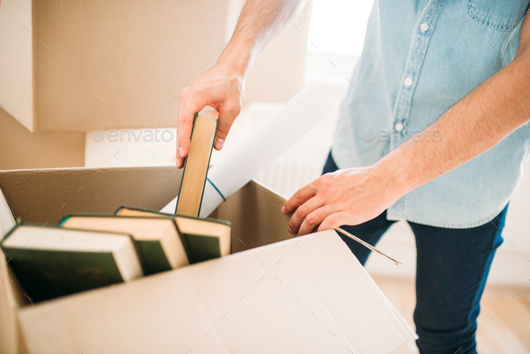 Young man unpacking cardboard boxes, housewarming - Stock Photo - Images