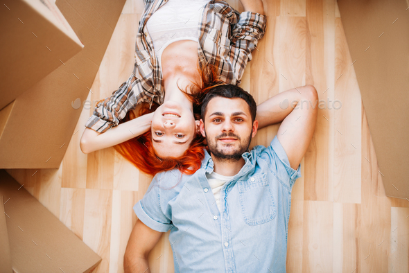 Couple lies on the floor, top view, new house - Stock Photo - Images