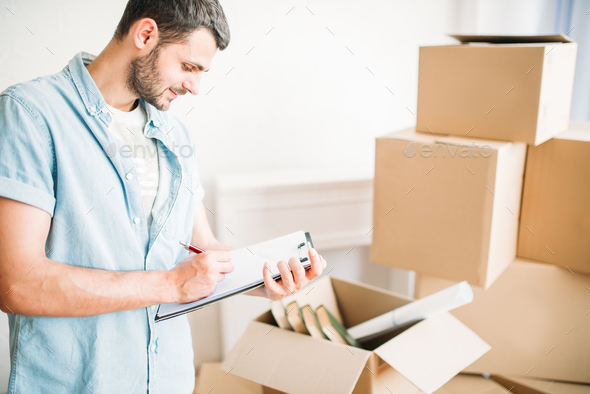 Man with notebook among boxes, housewarming - Stock Photo - Images