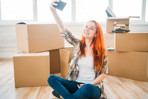 Woman among cardboard boxes makes selfie on camera - Stock Photo - Images